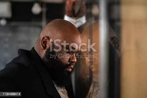 668329720 istock photo Frustrated afro man feeling bad standing near the window 1134468414