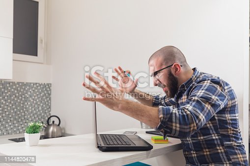 593328060istockphoto Frustrated and Angry Young Businessman Yelling at the Laptop 1144820478