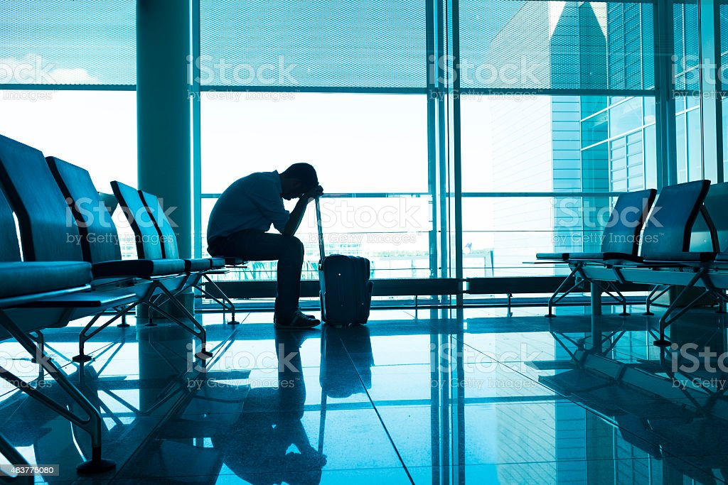Frustrated and tired passenger waits for delayed plane at airport stock photo