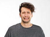 istock Frustrated and worried young man portrait in grey t-shirt 1045297442