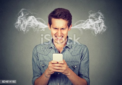 istock Frustrated angry man reading a text message on his smartphone blowing steam coming out of ears 824614192