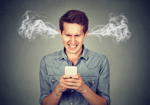 귀에서 나오는 증기를 불고 그의 스마트폰 문자 메시지를 읽고 좌절된 화난 사람 - 악한 뉴스 사진 이미지