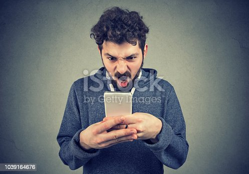 824614192 istock photo Frustrated angry man reading a text message on his smartphone feeling frustrated 1039164676