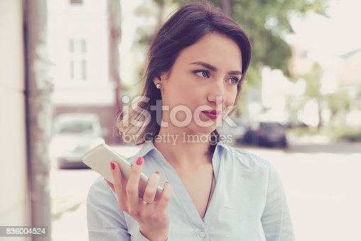 istock Frustrated annoyed sad woman with mobile phone standing outside in the street with an urban background 836004524