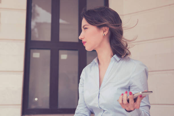 frustrated annoyed sad woman with mobile phone standing outside apartment condo - inpatient stock pictures, royalty-free photos & images
