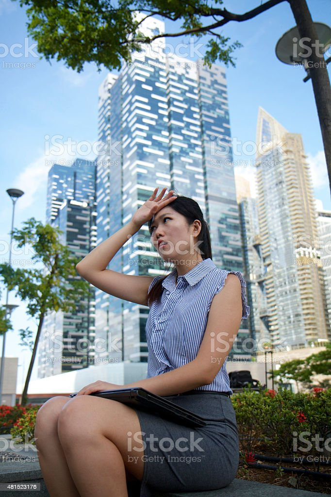 Frustrated asian businesswoman working outdoors stock photo