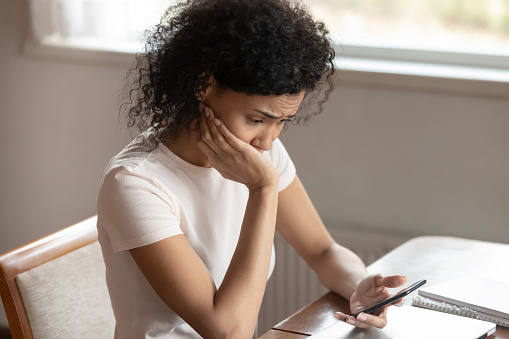 istock Frustrated biracial woman having operational cellphone problems 1186579771