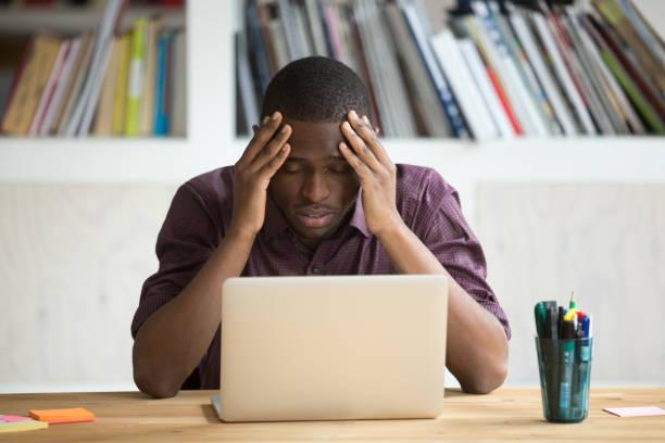 frustriert schwarzer mann nach scheitern mit laptop sitzt deprimiert - fehler problem stock-fotos und bilder