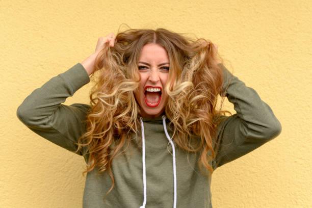 frustrerad blond kvinna slet hennes långa hår - kvinna ventilationssystem bildbanksfoton och bilder