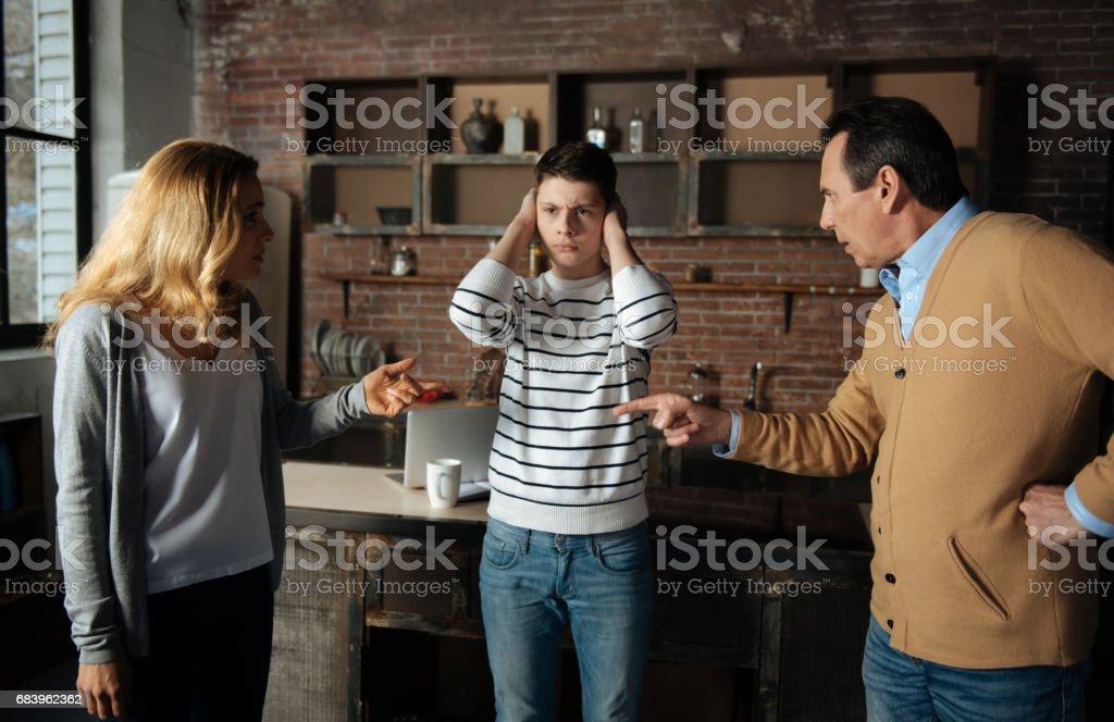Frustrated boy standing between his parents stock photo