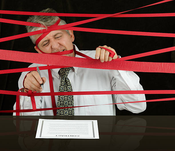 Frustrated business man caught in red tape stopping progress Frustrated angry man caught in political bureaucratic red tape regulations as he struggles to reach the contract in front of him awaiting his signature so he can move forward with successful business bureaucracy stock pictures, royalty-free photos & images