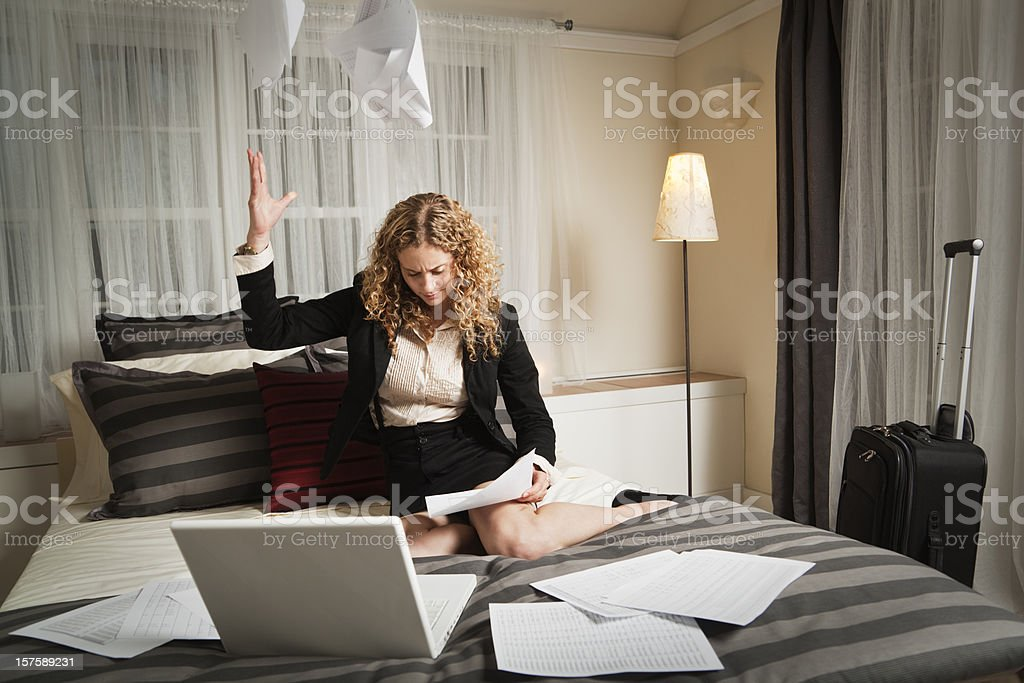Frustrated Business Traveler Working Late in Hotel Room with Paperwork royalty-free stock photo