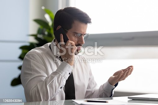 502723248 istock photo Frustrated businessman angry over bad news message talking on smartphone. 1263543094