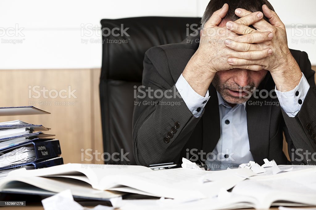 Frustrated businessman at desk with head in hands royalty-free stock photo