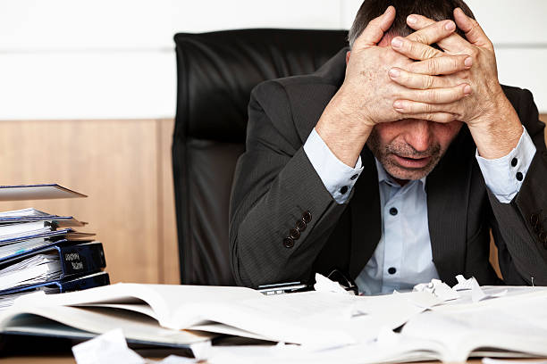 Frustrated businessman at desk with head in hands stock photo