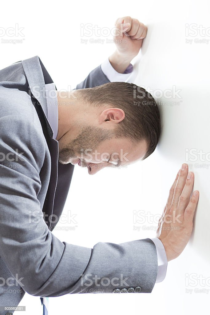 Frustrated Businessman Banging Head, Fist Against Wall on White Background stock photo