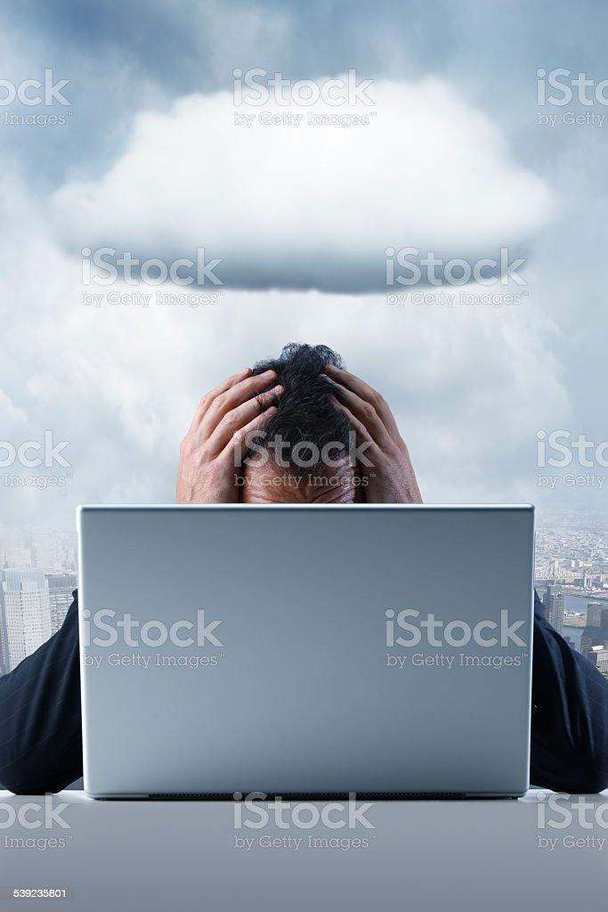 Frustrado hombre de negocios en un ordenador con una sombra sobre su foto de stock libre de derechos