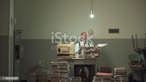 Frustrated vintage style businessman working in a rundown office, he is overloaded with papework