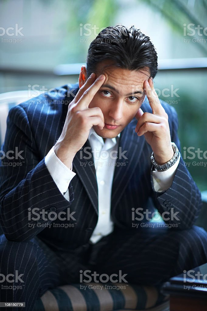 Frustrated Businessman Sitting and Holding Head in Hands royalty-free stock photo