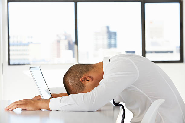 frustrated businessman sitting at desk in office using laptop - man face down stock pictures, royalty-free photos & images