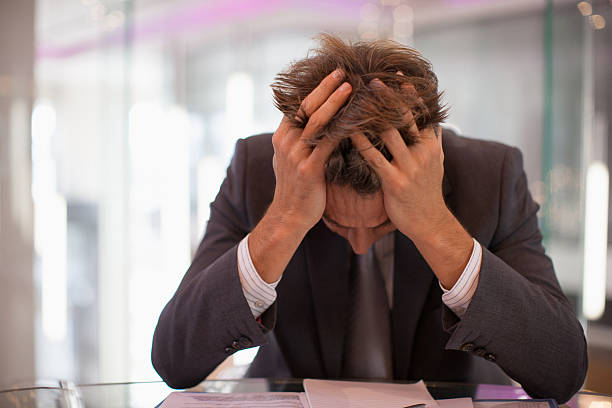 Frustrated businessman sitting at desk with  head in hands  head in hands stock pictures, royalty-free photos & images