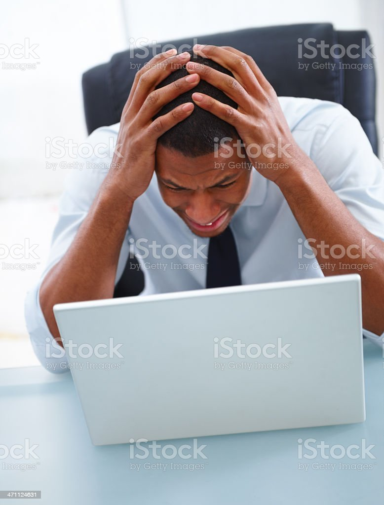 Frustrated businessman sitting in front of a laptop royalty-free stock photo