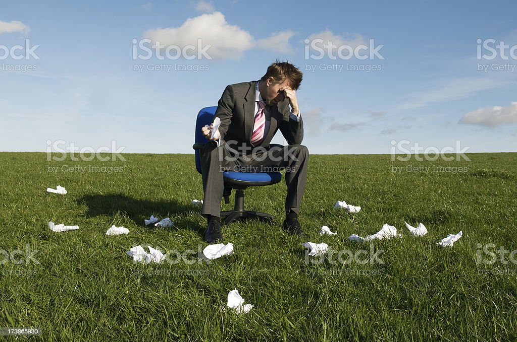 Frustrated Businessman Sitting in Meadow with Rejected Crumpled Paper royalty-free stock photo