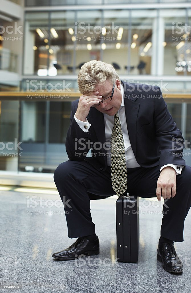 Frustrated businessman sitting on briefcase royalty-free stock photo