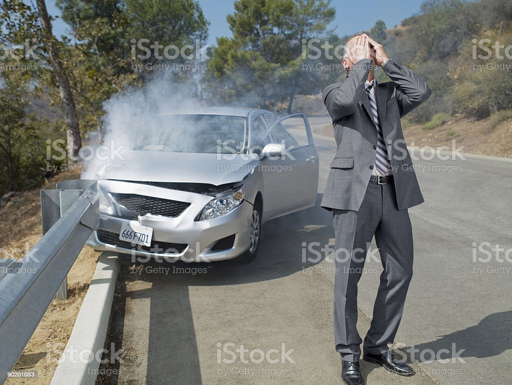 Frustrated businessman standing next to car wrecked on guardrail stock photo