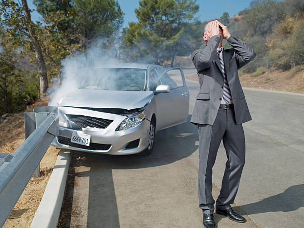 frustrated businessman standing next to car wrecked on guardrail - car accident stock photos and pictures
