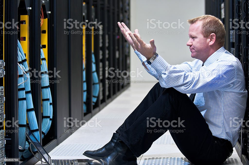 Frustrated businessman staring at row of servers stock photo