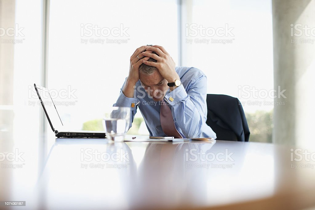 Frustrated businessman with head in hands at desk stock photo