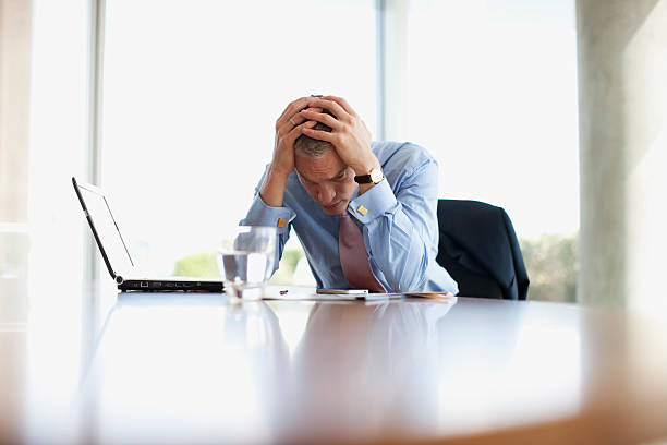 Frustrated businessman with head in hands at desk  head in hands stock pictures, royalty-free photos & images