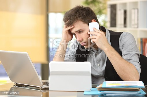 626916886istockphoto Frustrated businessman with multiple devices 622178550