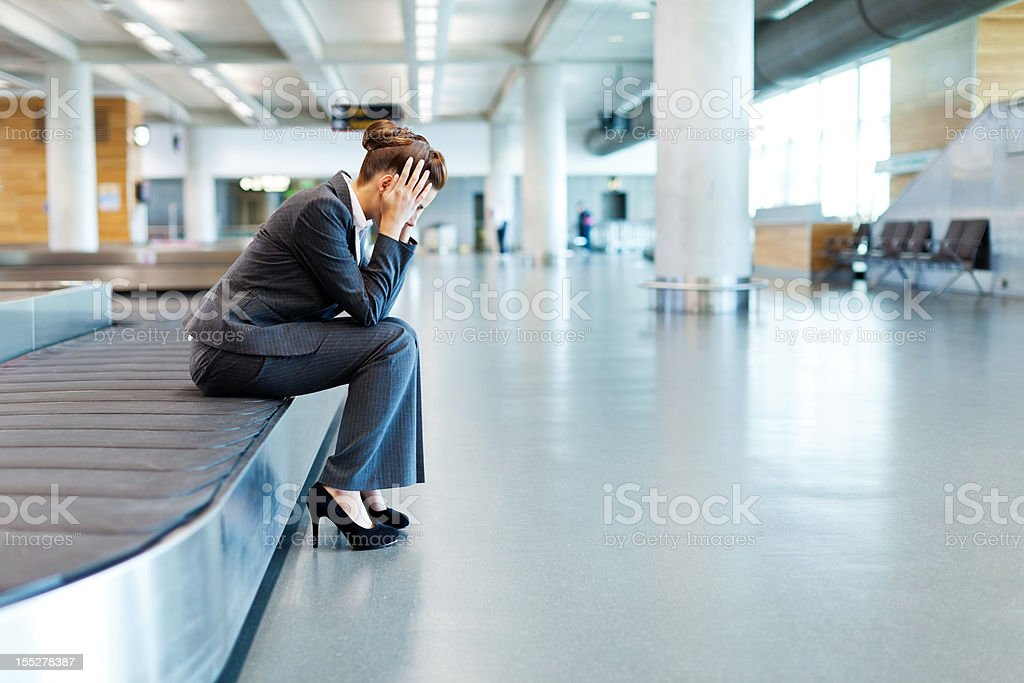 Frustrated Businesswoman Sitting at Baggage Claim stock photo