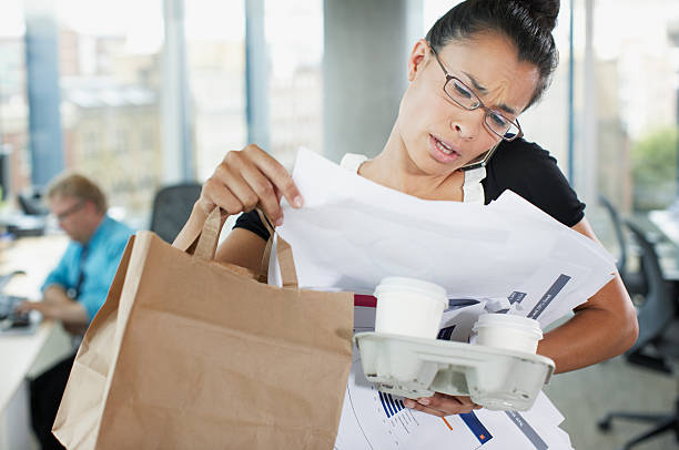 Frustrated businesswoman talking on cell phone with paperwork and coffee  multi tasking stock pictures, royalty-free photos & images