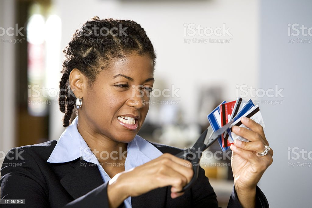 Frustrated Businesswomen Cutting up Credit Cards stock photo