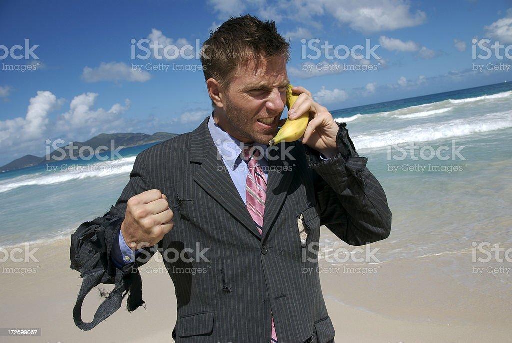 Frustrated Castaway Businessman Talks on Mobile Banana stock photo