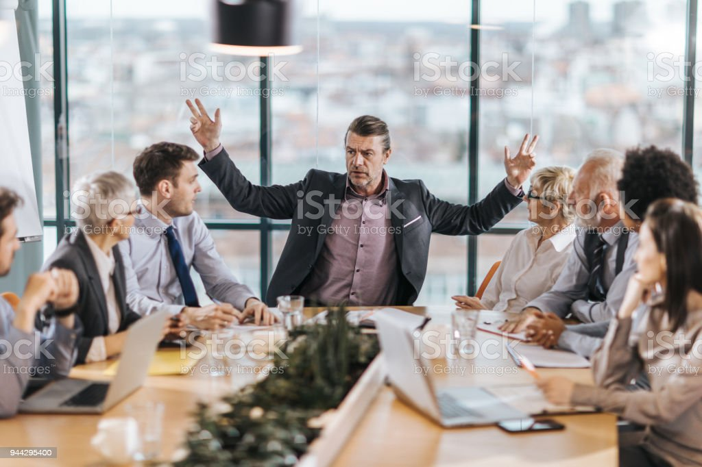 Frustrated CEO is angry at his colleagues during a meeting in the office. stock photo