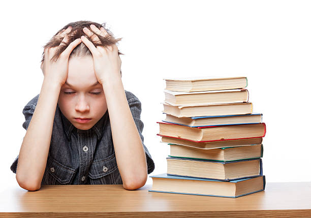 Frustrated child with learning difficulties Portrait of frustrated schoolboy sitting at a desk with books holding his head having learnind problems illiteracy stock pictures, royalty-free photos & images