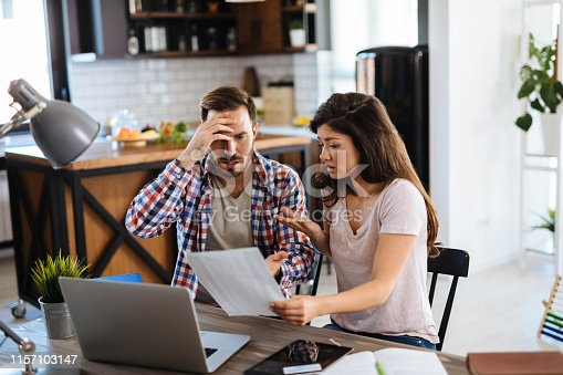 istock Frustrated couple checking bills at home using laptop 1157103147