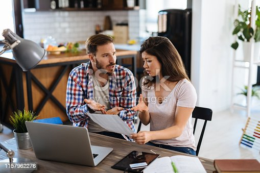 istock Frustrated couple checking bills at home using laptop 1157962276