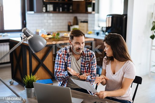istock Frustrated couple checking bills at home using laptop 1158435833