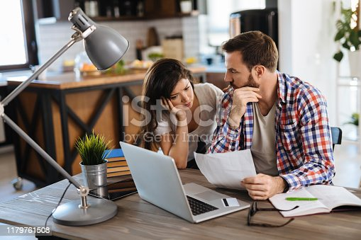 Frustrated couple checking bills at home using laptop