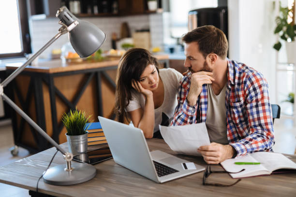 Frustrated couple checking bills at home using laptop stock photo