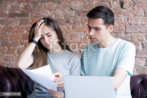 istock Frustrated couple checking bills 1036274142
