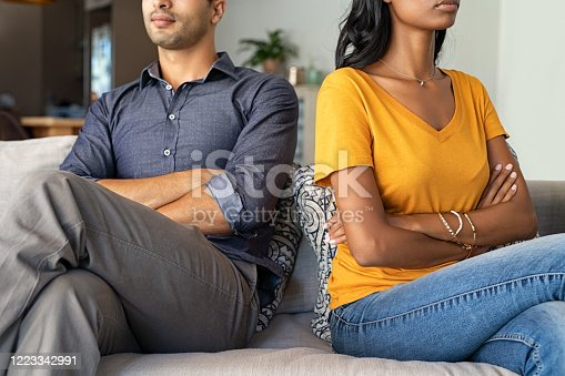 Middle eastern couple sitting back to back after a fight on the sofa. Young indian couple in fight with arms crossed sitting on couch after quarrel at home. Young mixed race woman and his boyfriend sitting next to each other angry.