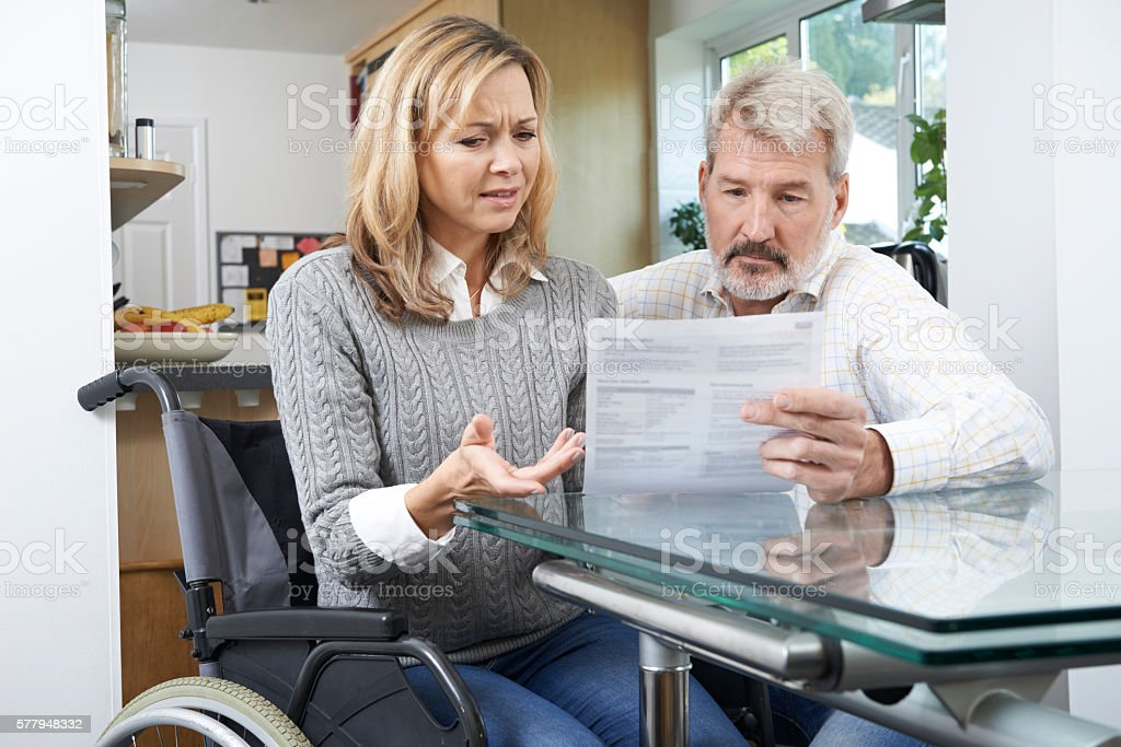 Frustrated Couple With Woman In Wheelchair Reading Letter stock photo