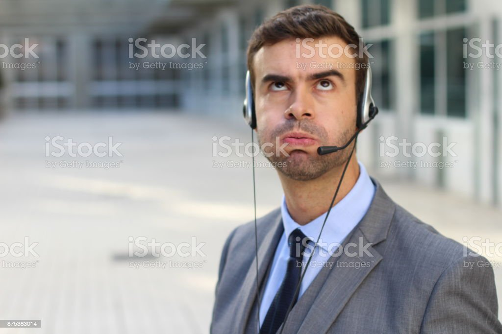Frustrated customer service worker rolling his eyes stock photo