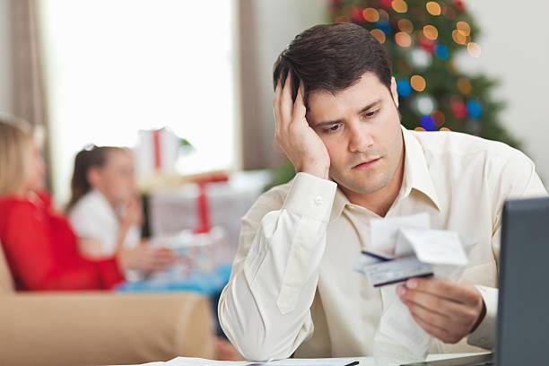 frustrato padre guardando le ricevute e le fatture per natale - holiday and invoice family foto e immagini stock